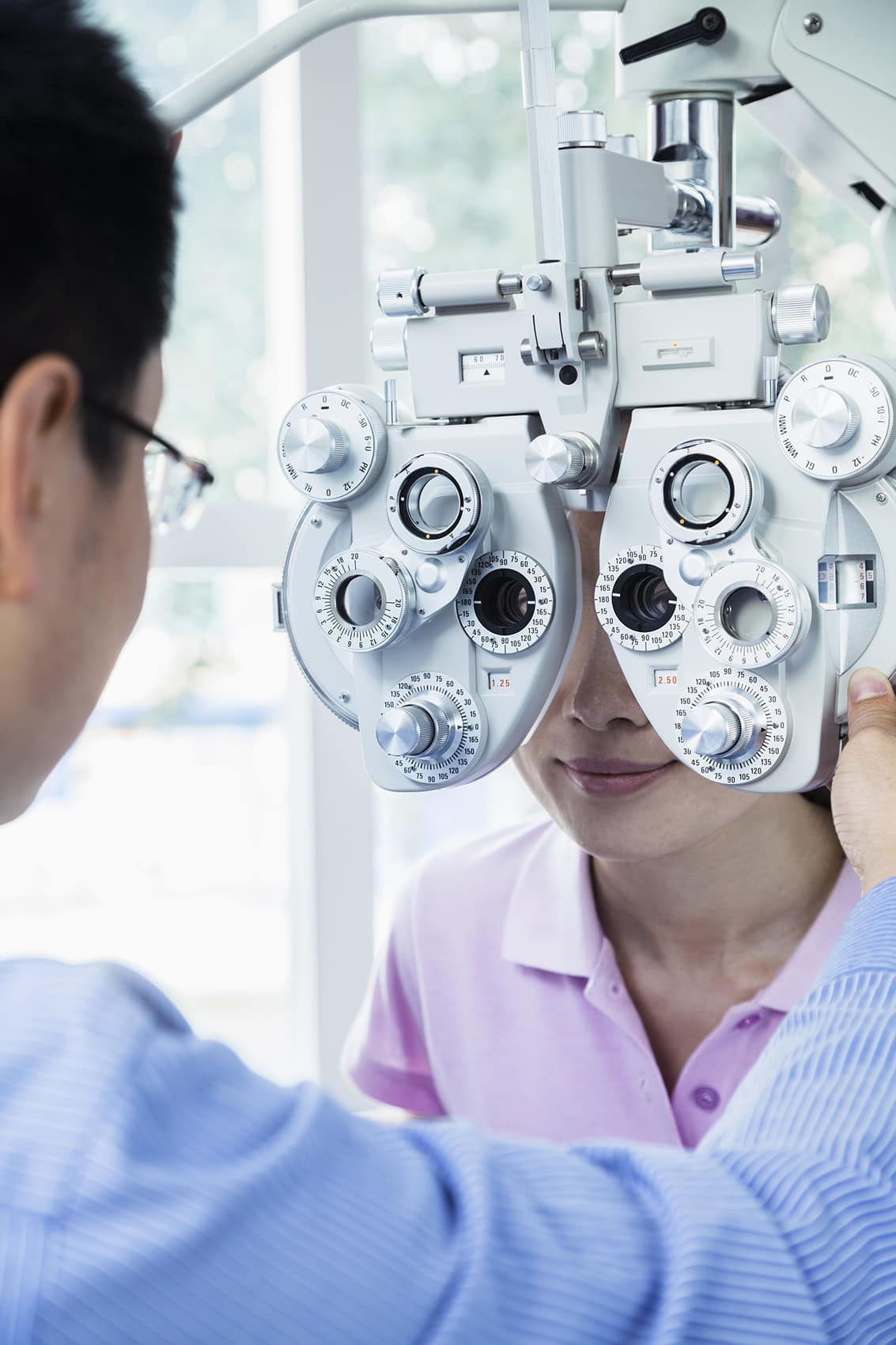 Optometrist doing an eye exam on young woman