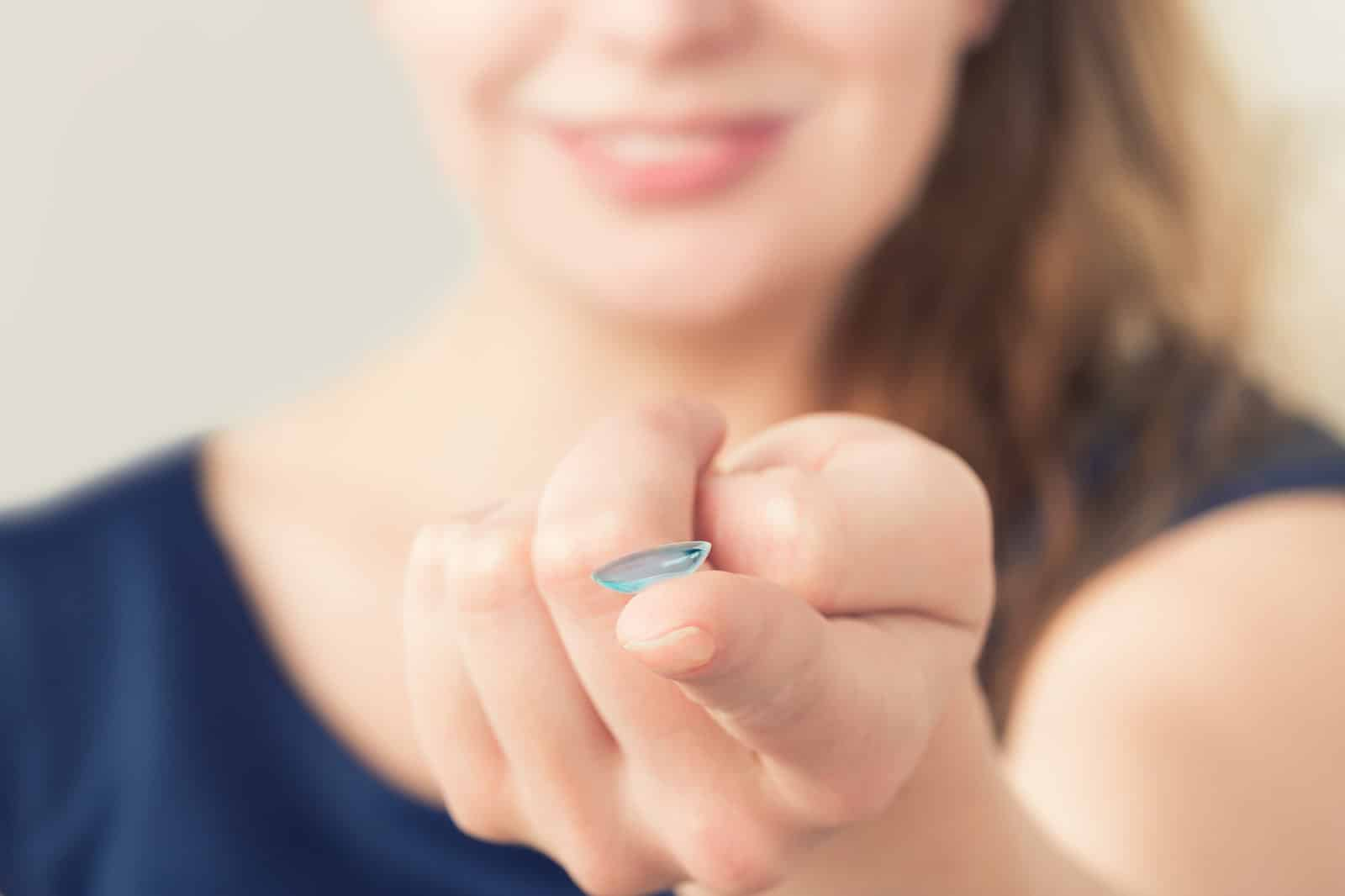 Woman inserting a contact lens in eye.